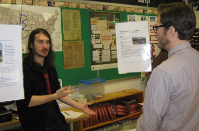 A student discusses his learning with Humanities teacher Wayland Cole