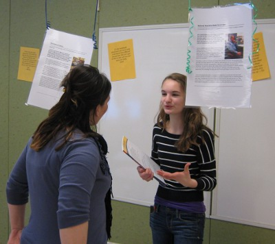 A student discusses her learning with Principal Amy Minor