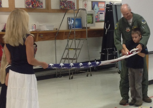 Colonel Palmer and his family demonstrate proper folding of the US flag