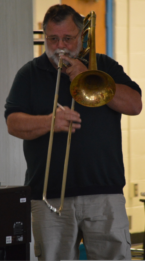 """Beloved bus driver and former music teacher Marty McRae performs """"Taps"""" at the assembly"""