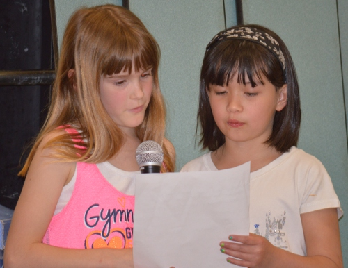 Second graders read a poem at the assembly