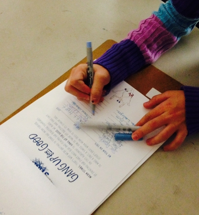 A student signs an anti-bullying pact